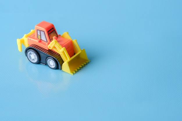Tractor toy on blue background and copy space