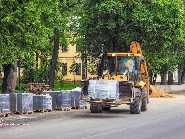 Трактор перевозит упаковочные единицы. дорожные работы.
