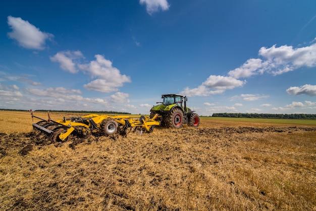 Трактор с дисковым культиватором, системой обработки почвы, обрезки и обработки пожнивных остатков с помощью двух рядов дисков.