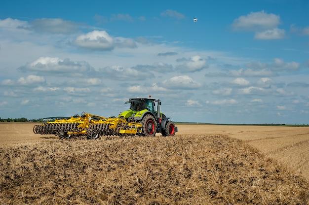 Трактор с тяжелой дисковой бороной в поле