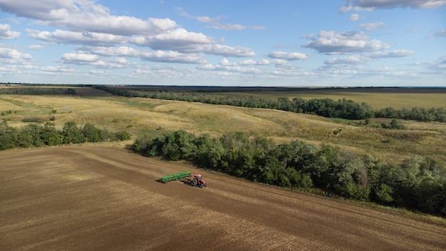 곡물 재배자가 있는 트랙터는 겨울 밀의 파종을 생산합니다.