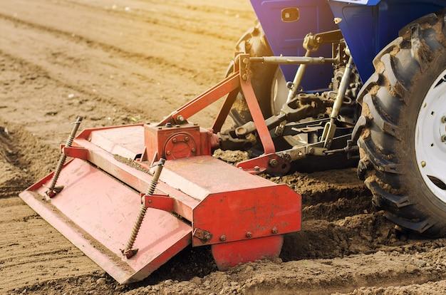 Трактор с фрезой рыхлит и перемешивает почву.