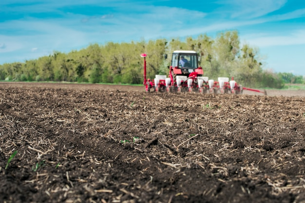 Трактор с сеялкой в поле в солнечный день