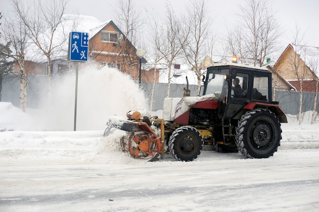 Tractor with plow, rotary mechanism clears the street of snow in the private sector.