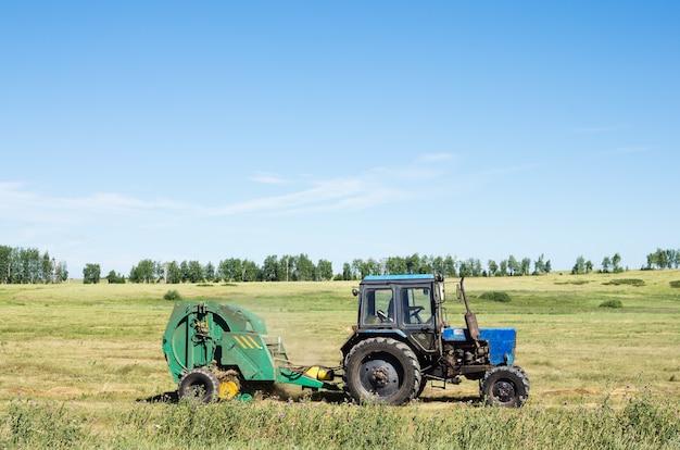 Трактор с прицепным штабелеукладчиком убирает с поля сено