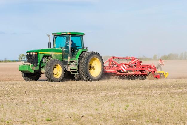 Трактор с прицепом вспаханной земли в поле