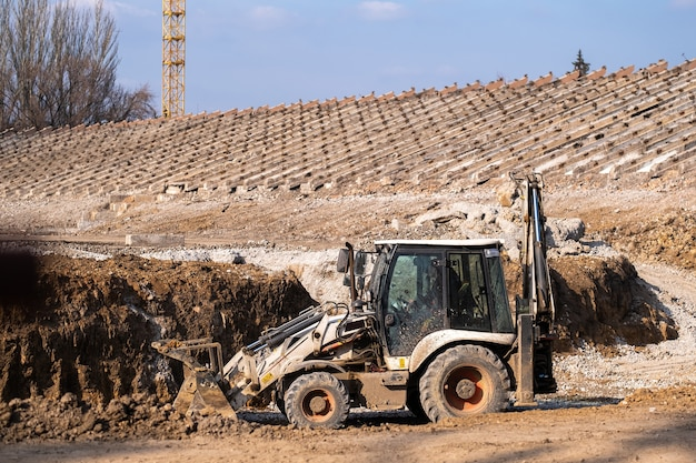 Tractor workig to construction of a new stadium. heavy industrial machinery build modern arena.