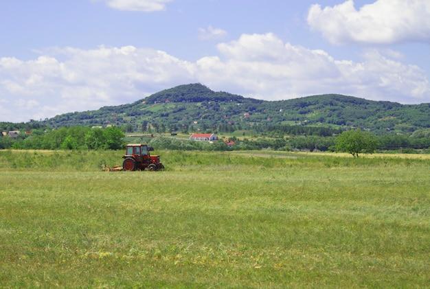Трактор работает в поле и собирает траву для колхоза.