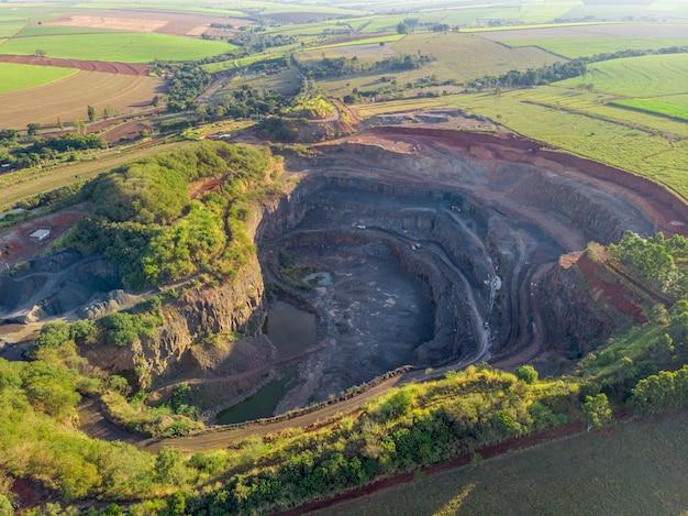 採石場の穴の中から石を取り除くトラクターとトラック。