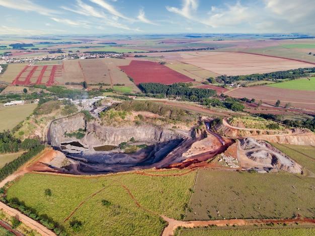 採石場の穴の中から石を取り除くトラクターとトラック