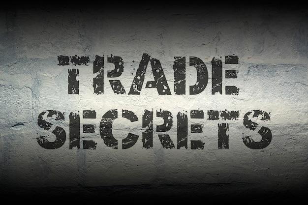 Trade secrets stencil print on the grunge white brick wall