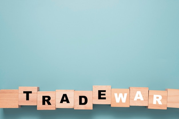 Trade war wording print screen on wooden block cube with blue background.