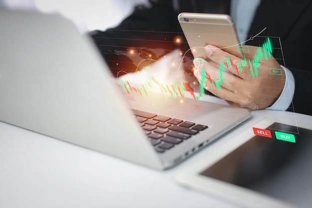 Trader or businessman hands showing virtual hologram price graph and indicator, red and green candlestick chart stock trading on laptop computer and smartphone. investing on stock concept.