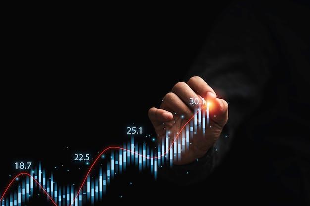 상인은 기술 투자 분석 개념을 위해 어두운 배경에서 주식 시장 그래프 차트를 그립니다.
