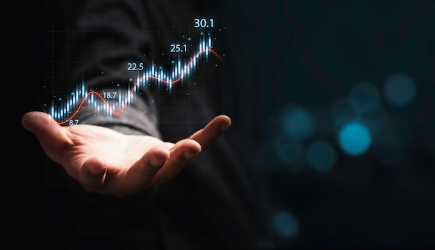 Trader hand holding smartphone with stock market graph chart on dark background for technical investment analysis concept.