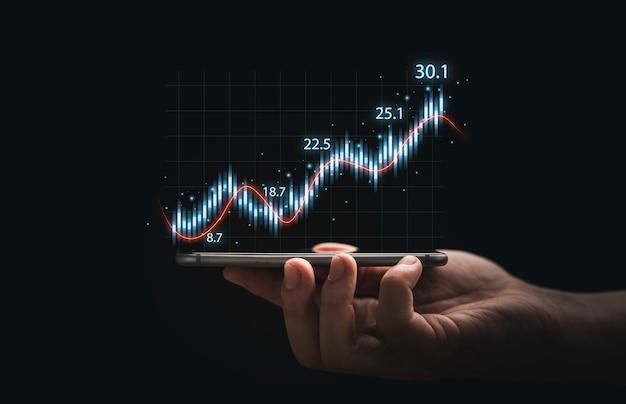기술 투자 분석 개념을 위해 어두운 배경에 주식 시장 그래프 차트가 있는 스마트폰을 들고 있는 트레이더.