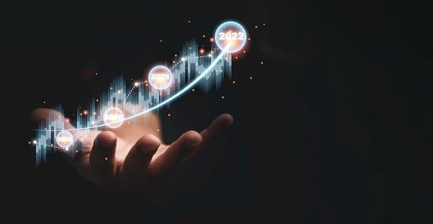 技術投資分析の概念のための暗い背景に仮想株式市場のグラフチャートを持っているトレーダーの手。