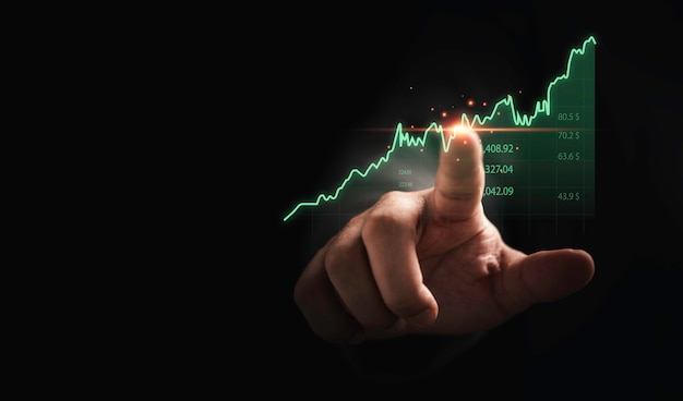 Trader hand touching to stock market graph chart on dark background for technical investment analysis concept.