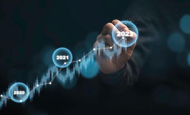 기술 투자 분석 개념에 대한 어두운 배경에 가상 주식 시장 그래프 차트를 작성하는 상인 손.