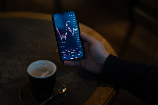 Trader or investor reading financial news and analyzing real time stock market data while sitting outdoors and drinking coffee, male hand holding smartphone with live forex chart on screen