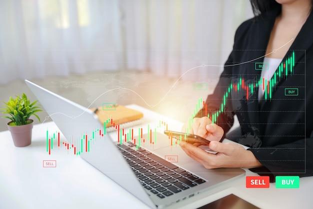 가상 홀로그램 가격 그래프와 표시기, 빨간색 및 녹색 촛대 차트 주식 거래를 랩톱 컴퓨터와 스마트폰에서 보여주는 상인 또는 사업가 손. 주식 개념에 투자합니다.