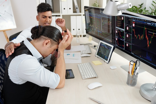 投資中にヘッジファンドの多くのお金を失った彼の同僚を安心させようとしているトレーダー