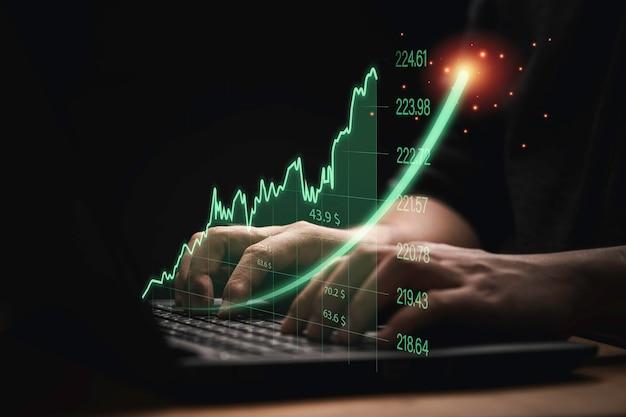 가상 투자 그래프와 차트가 증가하는 컴퓨터 랩톱을 사용하는 트레이더는 트레이더 개념에 따른 주식 시장 분석 추세 및 기술에 대한 차트입니다.