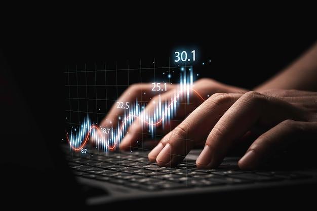 투자 개념에 대한 분석 주식 시장을 위한 기술 그래프와 차트가 있는 노트북 컴퓨터를 사용하는 거래자.