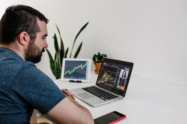 Команда трейдеров делает анализ фондового рынка с помощью видеозвонка на ноутбуке