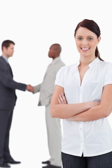 Tradeswoman with arms folded and hand shaking trading partners behind her against a white background