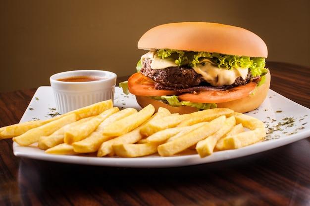 Традиционный гамбургер, соус и картофель на деревянном столе