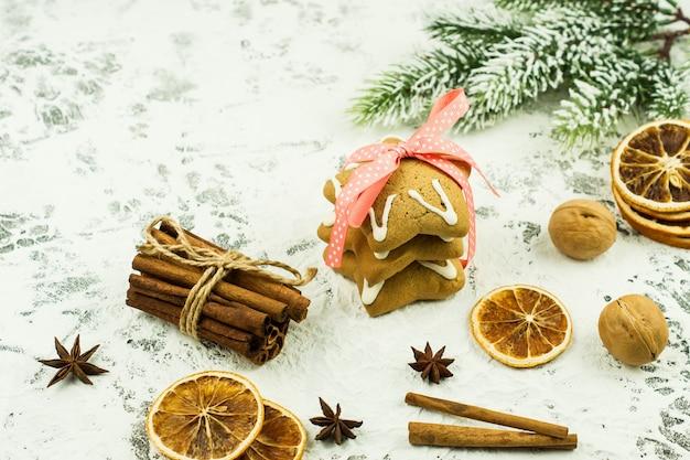 전통적인 크리스마스와 새해 음식과 향신료. 흰색 배경에 흩어져 있는 계피 스틱, 말린 오렌지, 진저브레드 쿠키, 아니스 별