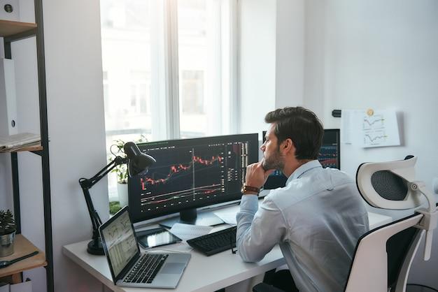 Торговля на мировых рынках молодой брокер фондового рынка анализирует данные и графики на нескольких компьютерах