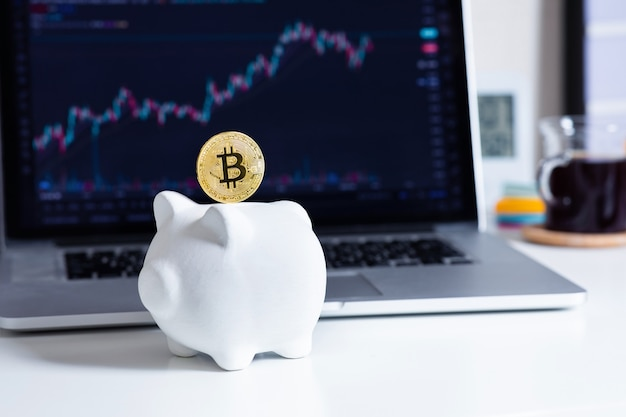 Trading or savings cryptocurrency with bitcoin and piggy bank and blur of chart price on computer
