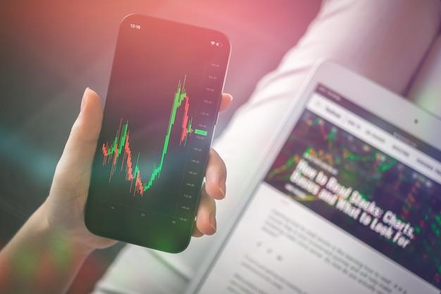 Торговля на фондовом рынке с помощью смартфона дома. торговая онлайн-концепция. женщина брокер инвестиционный фон фото