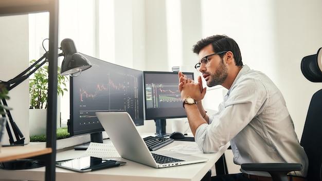 거래 전략 거래 차트 분석을 보고 있는 안경을 쓴 성공적인 젊은 거래자