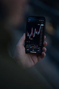 Trading wherever you are. male hand using mobile app on smartphone for reading financial news in real time and checking stock market data in real time. selective focus on screen with forex graph chart