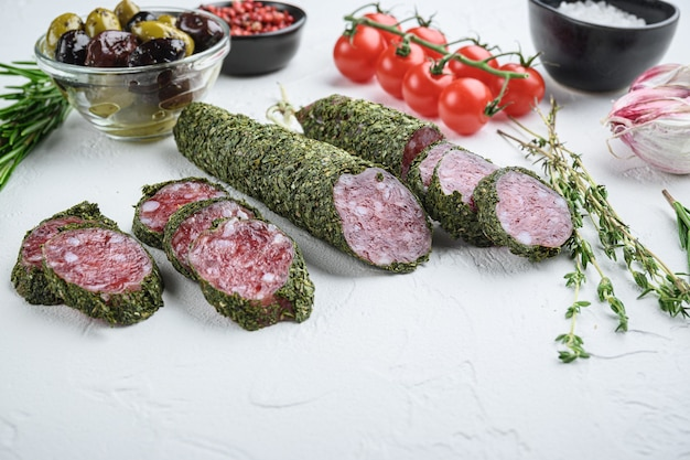 Traditianal fuet sausage in herbs with ingredients on white textured table.