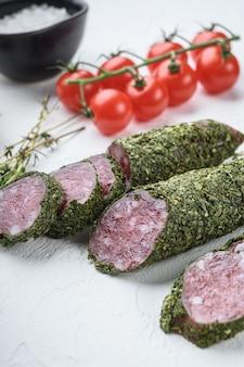 Традиционная колбаса fuet в травах с ингредиентами на белом текстурированном фоне.