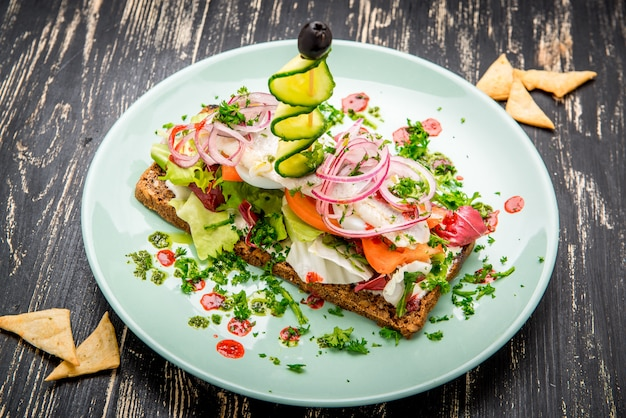 Традиция датского открытого бутерброда сморреброд с сельдью, огурцом и луком.