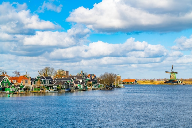 Tradition dutch houses in saandijk with the river zaan and a wooden windmill in netherlands