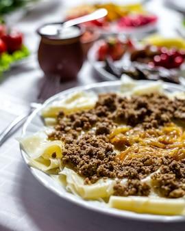 ミンディ肉オニオンプレーンヨーグルトサイドビューと伝統的な料理のヒンガル