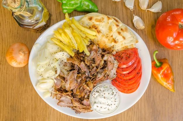 Traditiona greek pita gyros with meat, fried potatoes, tomato, onion