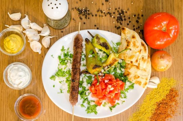 Traditiona greek pita souvlaki with meat, fried potatoes, tomato, onion