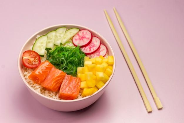 Традиционная гавайская красная рыба с рисом, редисом, огурцом, помидорами и водорослями. чаша будды. диетическое питание. плоская планировка. бамбуковые палочки для еды