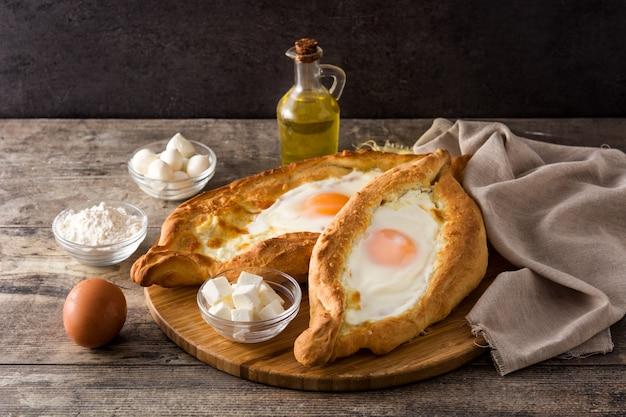 Традиционный грузинский хачапури с сыром и яйцом на деревянном столе