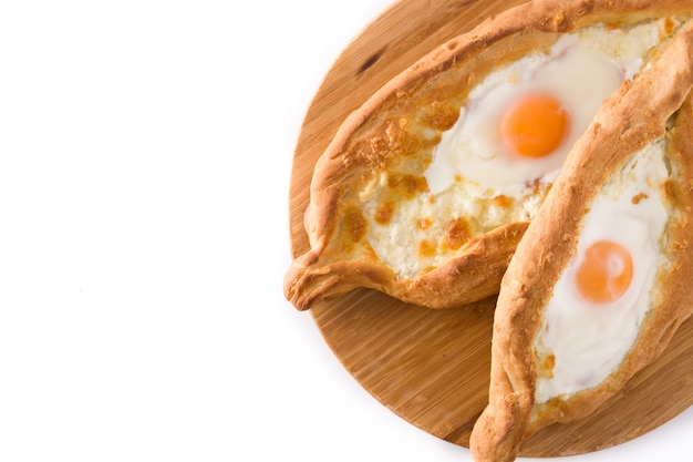 Traditional adjarian georgian khachapuri with cheese and egg isolated on white. top view