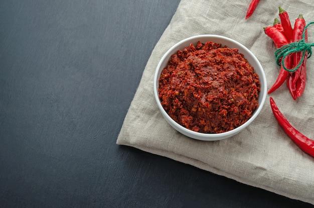 Traditional adjika hot chili pepper sauce paste harissa. tunisia, georgian and arabic cuisine. horizontal orientation. copy space