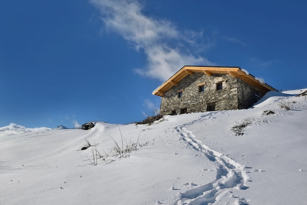 Традиционное альпийское шале на вершине снежной горы под голубым небом