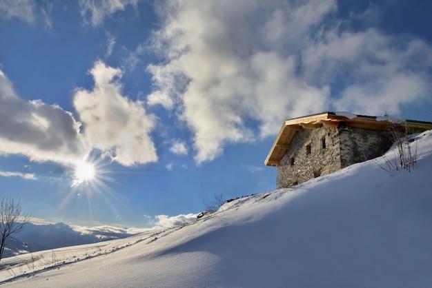 하늘에서 일출 아래 눈 덮인 산 꼭대기에서 전통적인 알파인 샬레